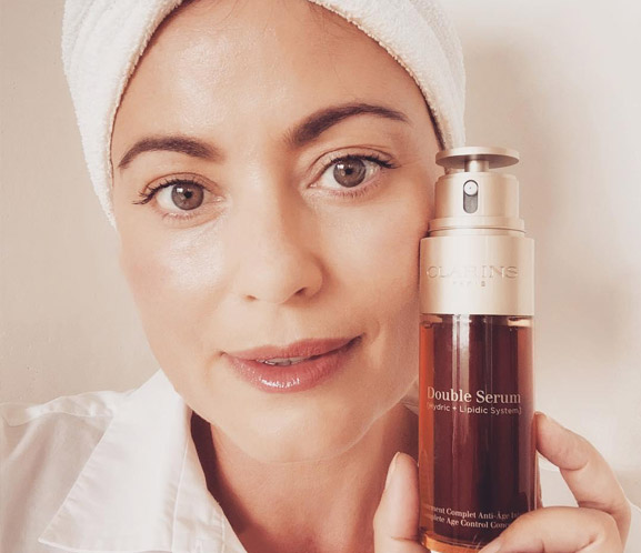 Clarins user holding Double Serum by face